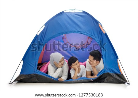 Picture of young family camping in the studio while lying together in the tent, isolated on white background