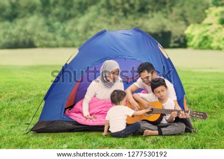 Picture of young family playing a guitar while enjoying their holiday in the campground