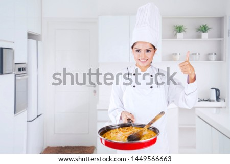 Picture of young female chef showing thumb up and tasty food in a pan in the kitchen