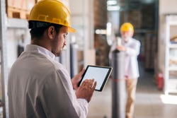 Picture of young focused male manager standing in factory and holding tablet. Dressed in white coat with helmet on his head.