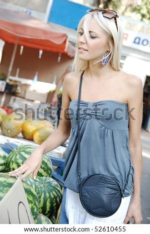 picture of young girl on a market choosing  a watermelon