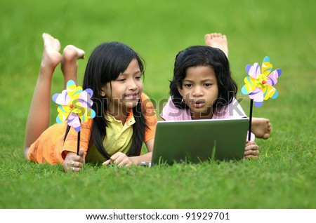 Picture of young girls from the southeast asia learning the technology from a laptop computer in green meadow