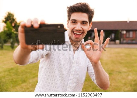 Picture of young happy man outdoors take a selfie by mobile phone with okay gesture.