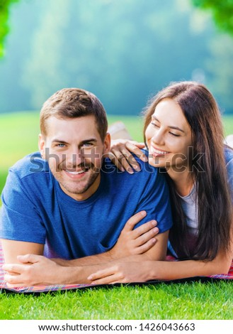 Picture of young happy smiling couple in love, lying together on a picnic blanket, outdoors at summer time.