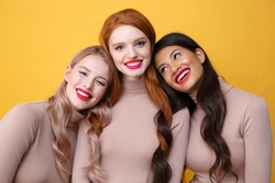 Picture of young happy three ladies with bright makeup lips standing over yellow background
