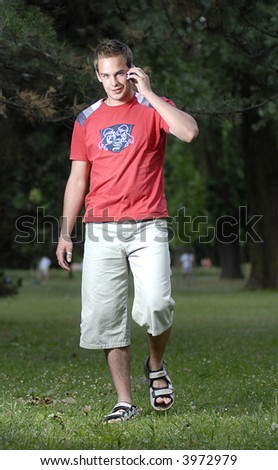 Picture of young leisure time dressed man with cell phone in park talking while walk