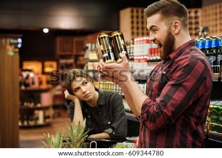 Picture of young loving couple in supermarket with shopping trolley choosing products. Dissatisfied woman looking at man holding beer.