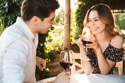 Picture of young loving couple sitting in cafe by dating outdors in park holding glasses of wine drinking talking with each other.