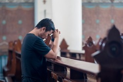 Picture of young man standing with clasped hands while praying to GOD in the church
