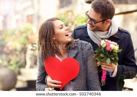 Picture of young man surprising woman with flowers and heart #502740346