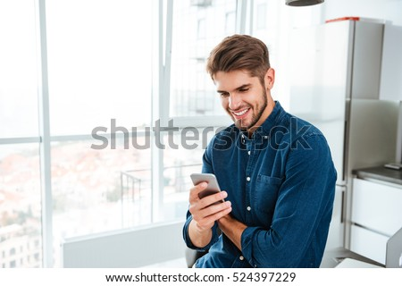 Shutterstock Picture of young man using a smartphone and smiling. Looking at smartphone.