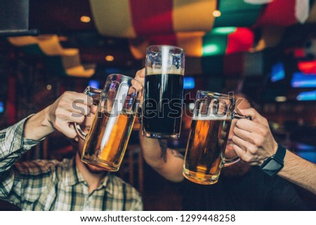 Picture of young men sitting in pub and holding mugs of dark and light beer together.