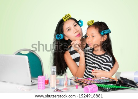 Picture of young mother doing makeup with her daughter while watching makeup tutorials in the studio