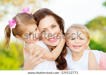 Picture of young mother hugging two little children, closeup portrait of happy family, cute brunette female with daughter and son outdoor in spring time, smiling faces, happiness and love concept - stock photo