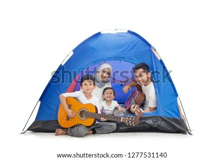 Picture of young Muslim family playing guitars in the tent while camping in the studio, isolated on white background