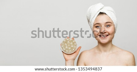 Picture of young positive woman hold body brush in hand and smile. White towel on head. After shower. Naked. Isolated on grey background