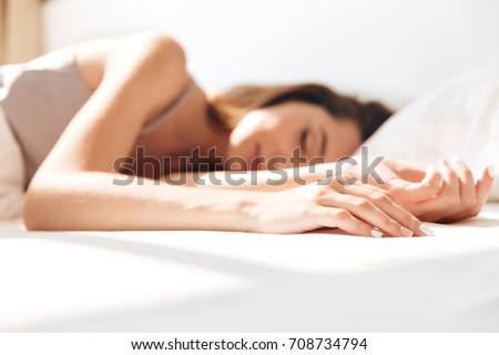 Picture of young smiling pretty lady sleep in bed indoors. Eyes closed.
