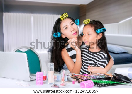 Picture of young woman doing makeup with her daughter while watching makeup tutorials in the bedroom