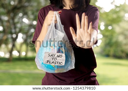 Picture of young woman holding a globe in the plastic bag while showing hands gesture to stop. Shot in the park
