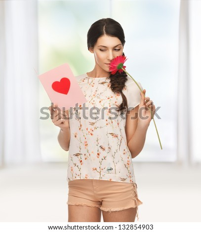 picture of young woman holding flower and  postcard.
