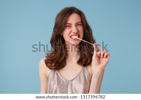 Picture of young woman pulling with effort tense gum from her mouth. Portrait of girl chewing a gum, having fun, in a party dress, isolated over blue background