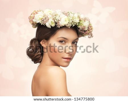 picture of young woman wearing wreath of flowers .