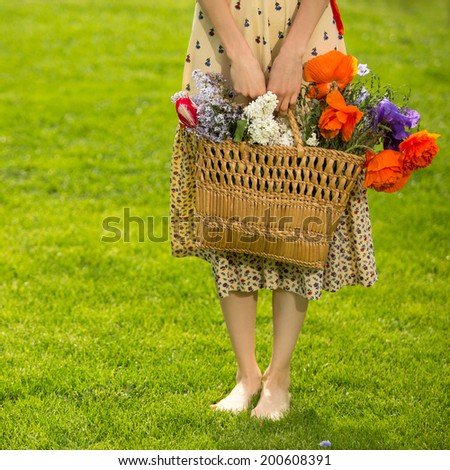 Picture of young woman with basket full of flowers. focus on hands and basket with flowers