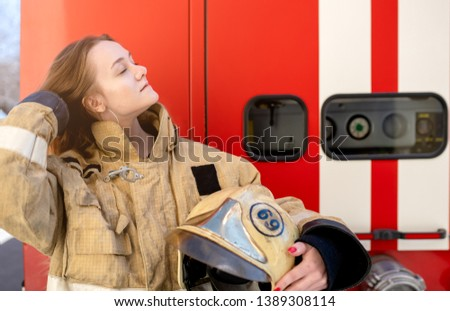 Picture on side of fire blonde woman standing near fire truck