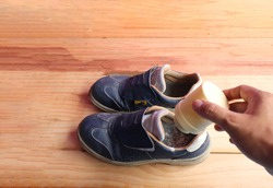Picture on the right hand holding a can of deodorant powder rich powder into safety shoes. To remove the smell of smelly shoes