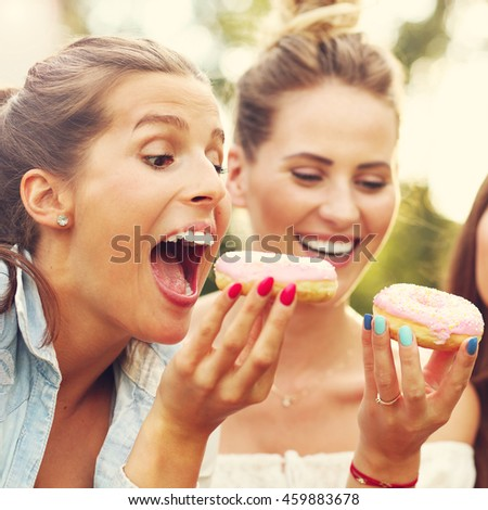 Picture presenting happy group of friends eating donuts outdoors #459883678