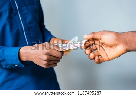 picture showing a man's hand giving money to someone. a man's hand stretching to collect money from another man