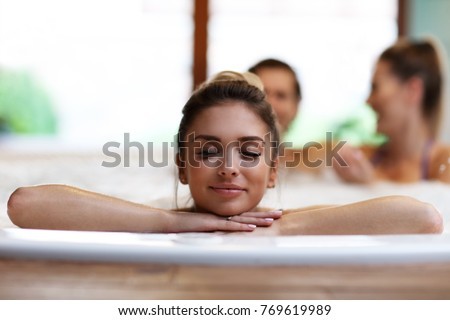 Picture showing group of friends enjoying jacuzzi in hotel spa
