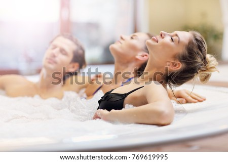 Picture showing group of friends enjoying jacuzzi in hotel spa #769619995