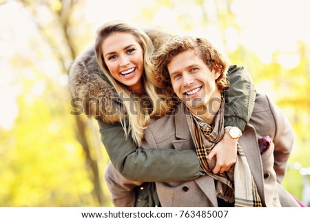 Picture showing happy couple walking in the forest during autumn