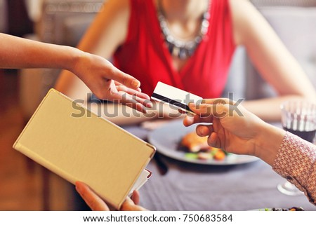 Picture showing people paying in restaurant by credit card reader