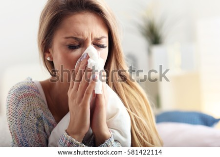 Picture showing sick woman sneezing at home