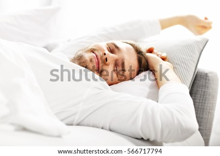 Picture showing young man stretching in bed