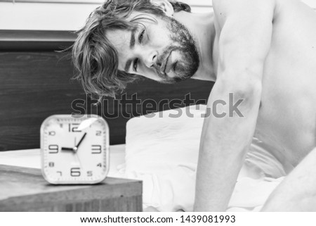 Picture showing young man stretching in bed. Bare feet of a man peeking out from under the cove. Relaxing in morning