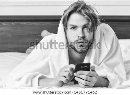 Picture showing young man stretching in bed. Feet of man sleeping in comfortable bed. Wake up morning