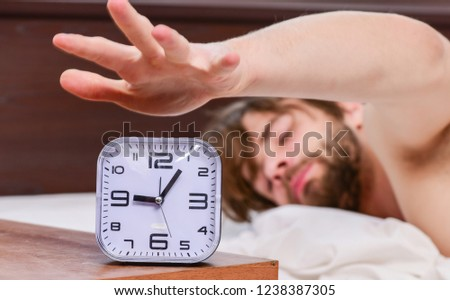 Picture showing young man stretching in bed. Guy is lying in the bed. Wake up morning