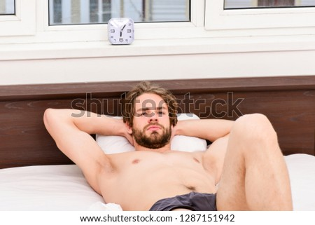 Picture showing young man stretching in bed. Handsome man using clock in bed after waking up in the morning.Hand turns off the alarm clock waking up at morning