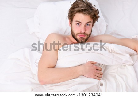 Picture showing young man stretching in bed. Man eyes are closed with relaxation. Morning bed active funny