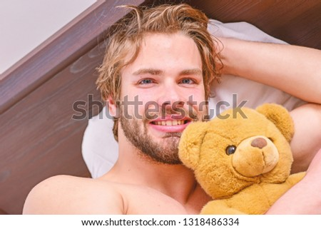 Picture showing young man stretching in bed. Man feeling back ache in the bed after sleeping. Man on the bed