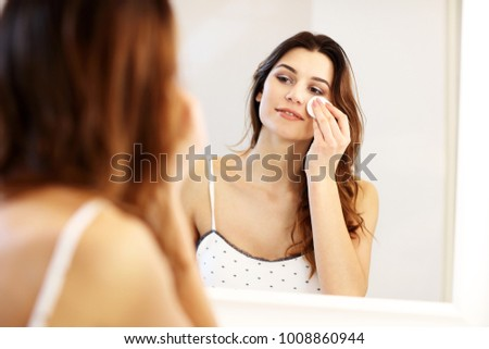 Picture showing young woman looking in bathroom mirror
