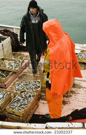 Picture shows two fishermen on a trawler boat on a rainy winter day