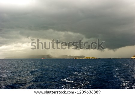 Picture taken from a yacht sailing away from the storm. Dark, heavy clouds hanging and rain pouring over an island in the distance; deep blue and stormy sea.