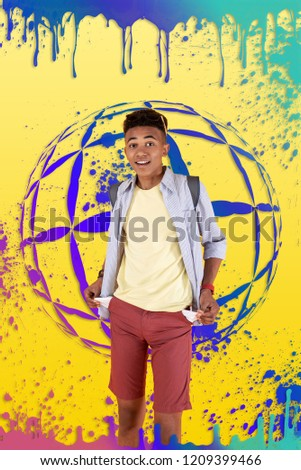 Picture with globe. Young traveler wearing shorts and striped shirt wearing blue backpack standing in front of picture with globe