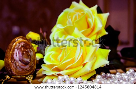 pictured in the photo artificial Easter brown egg and artificial yellow roses