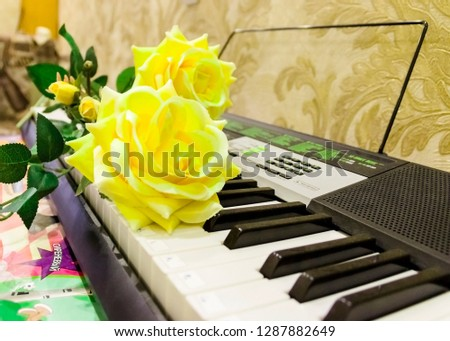 pictured in the photo big beautiful artificial yellow roses on the keys of the synthesizer