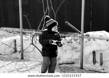pictured in the photo little boy walks in winter plays with a gun